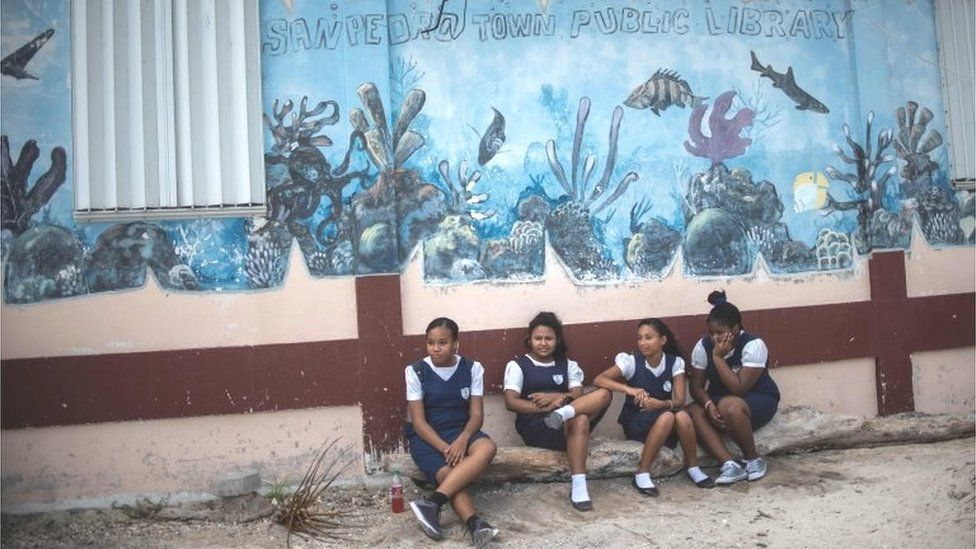Students remain next to a mural of the Hol Chan Marine Reserve coral reef in the outskirts of San Pedro village, in Ambergris Cay, Belize, on June 7, 2018