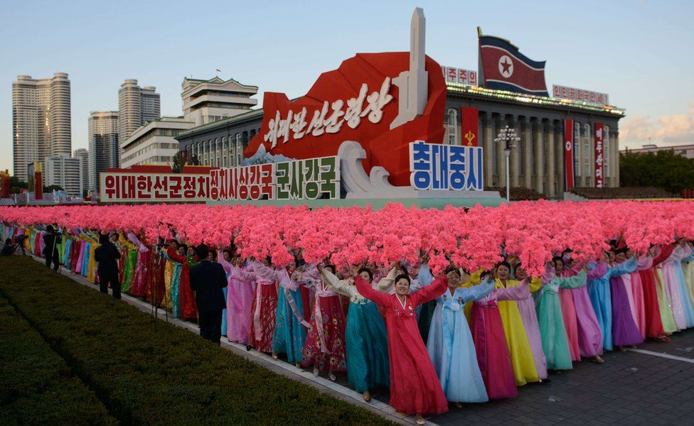 People holding up flowers during the military parade for the 70th anniversary of the founding Workers' Party, Pyongyang, North Korea - Saturday 10 October 2015