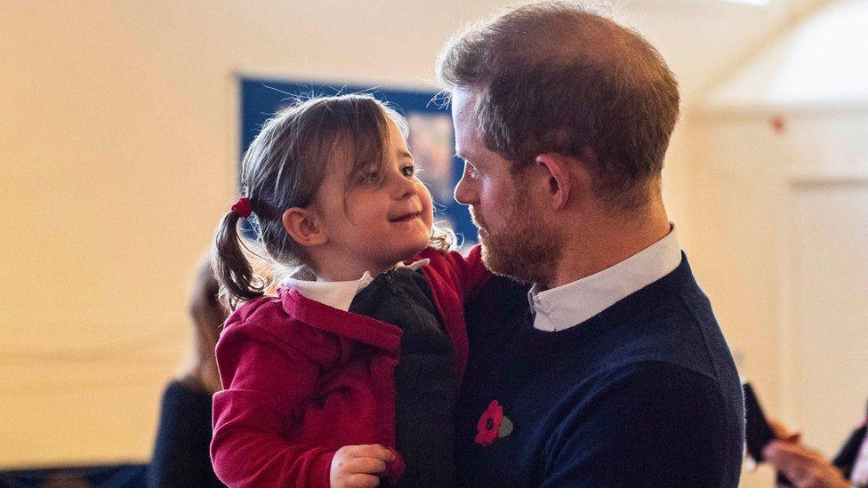 Prince Harry picks up a little girl at Windsor's Broom Farm Community Centre