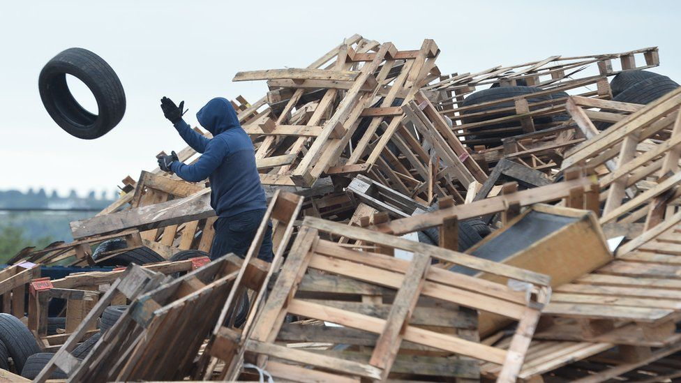 Tyres being removed from a bonfire at Avoniel in east Belfast on Monday
