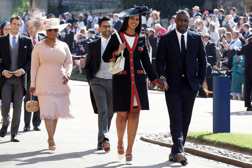 Idris Elba and Sabrina Dhowre, followed by Oprah Winfrey, arrive at St George's Chapel