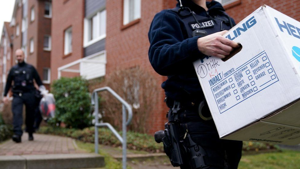 """Police officers carry evidence from a property following a raid in connection with the militant neo-Nazi group """"Combat 18"""" near Berlin in Wildau, Germany, 23 January 2020"""