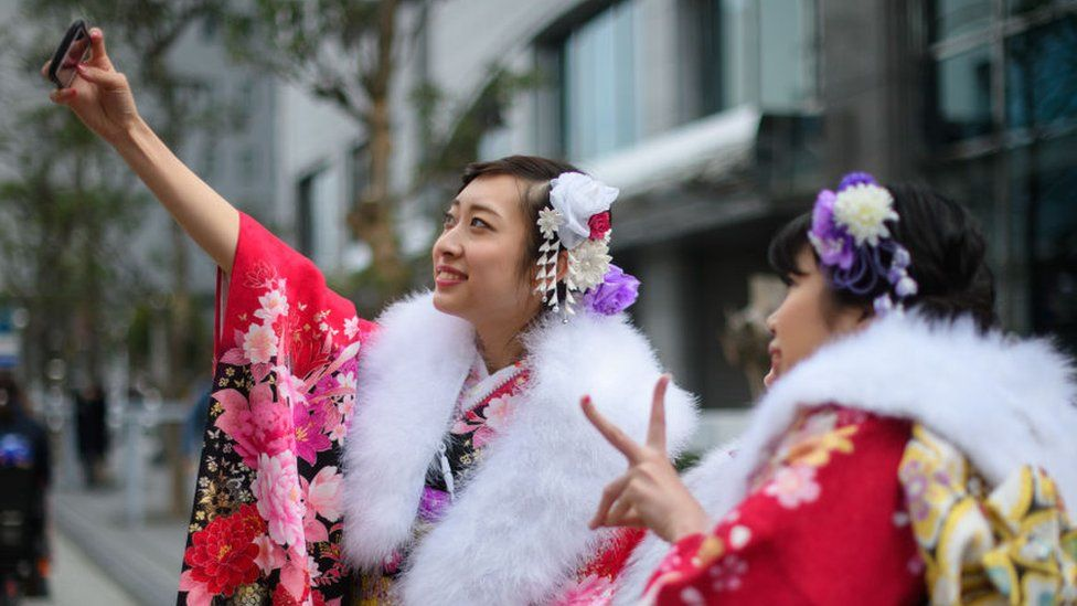 Women wearing kimonos take a selfie attending a Coming of Age ceremony on January 8, 2018 in Yokohama, Japan.