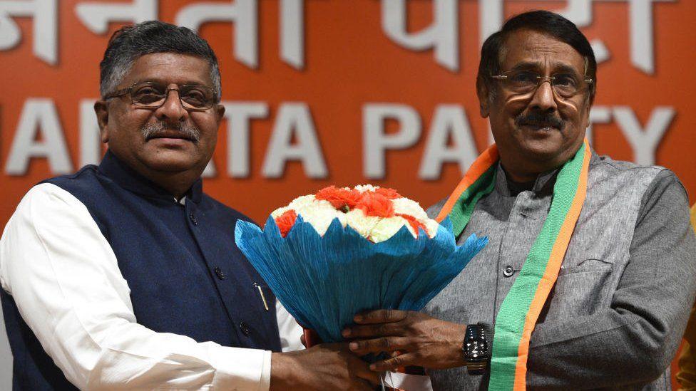 Union minister Ravi Shankar Prasad hands a bouquet of flowers to Tom Vadakkan