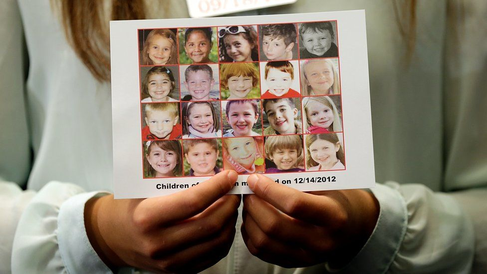 A woman holds up a memorial collage with pictures of the twenty child victims