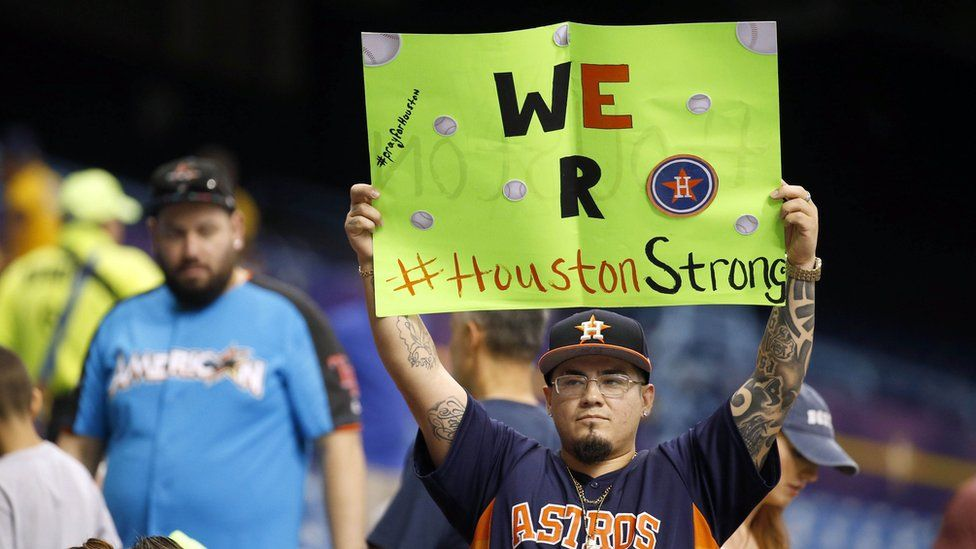 Houston Astros fan holds up a sign for those impacted with Hurricane Harvey