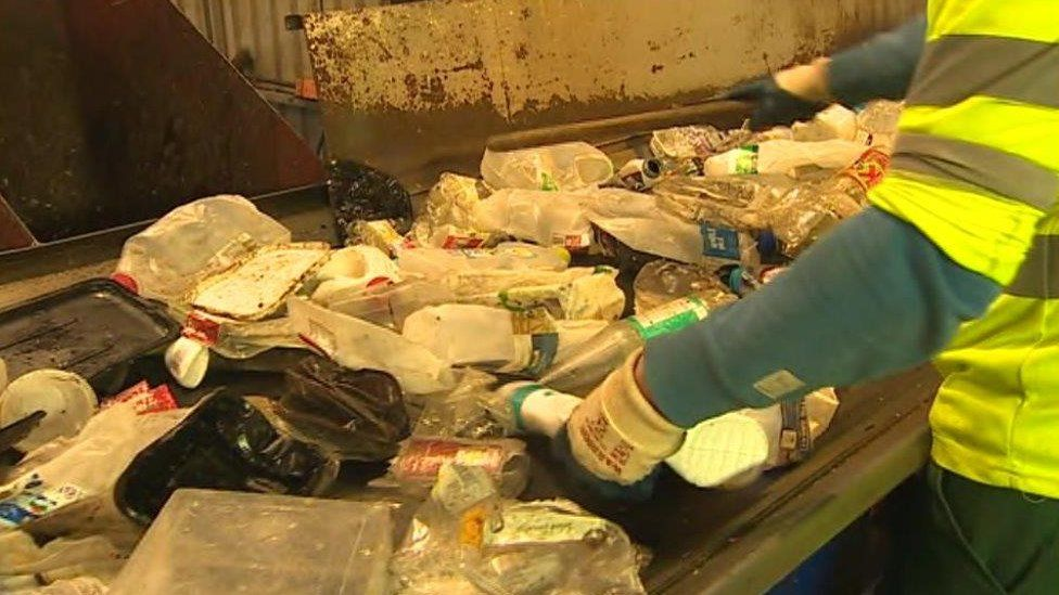 A worker sorts out recycling