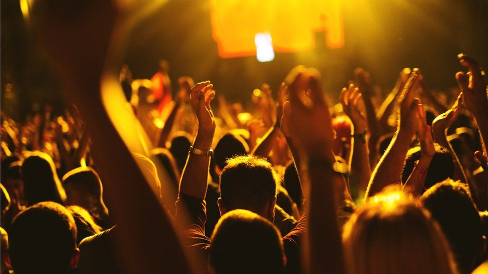Concert goers put their hands in the air for a band