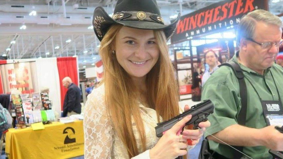 Maria Butina holds a gun wearing a cowboy hat at a gun convention