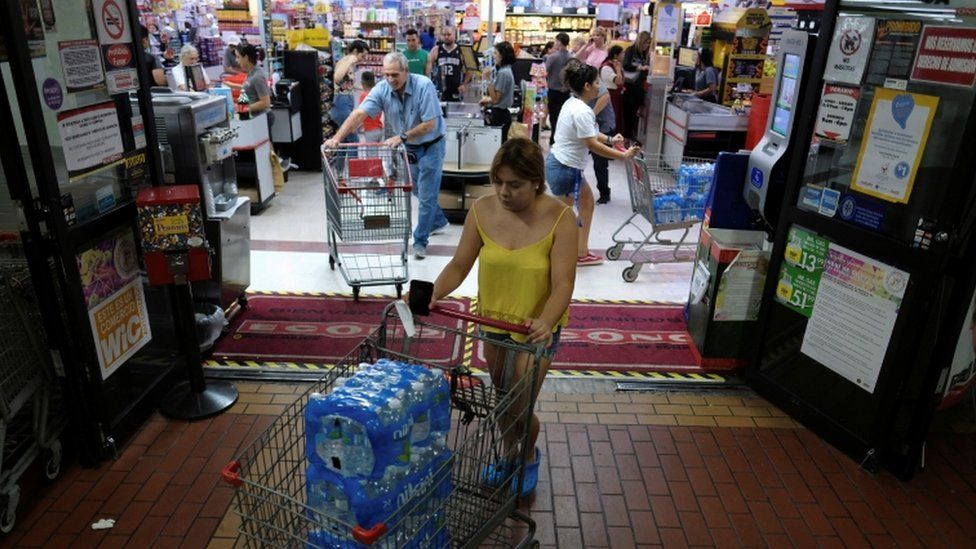 Shoppers buy food and water from a supermarket as Tropical Storm Dorian approaches in Cabo Rojo, Puerto Rico