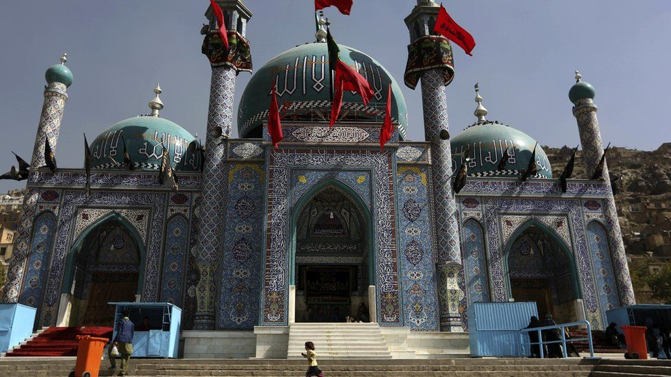 In this Sunday, Oct. 9, 2016. photo, an Afghan Shia girl runs in front of the Karti Sakhi shrine during a commemoration of Ashura in Kabul, Afghanistan,