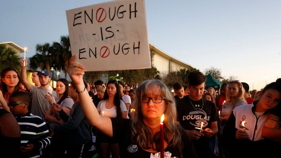 Mourners stand during a candlelight vigil for the victims of Marjory Stoneman Douglas High School shooting in Parkland, Florida on February 15, 2018.