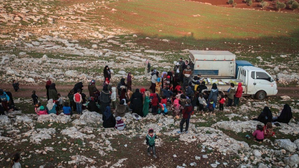 Displaced Syrians from Idlib province receive food aid from a truck