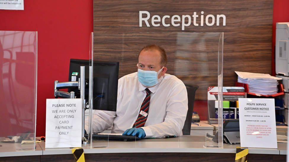 An employee wears PPE (personal protective equipment) including a face mask and gloves as a precautionary measure against COVID-19, as they sit behind perspex screen in the reception of a recently re-opened Vauxhall car dealership in north London