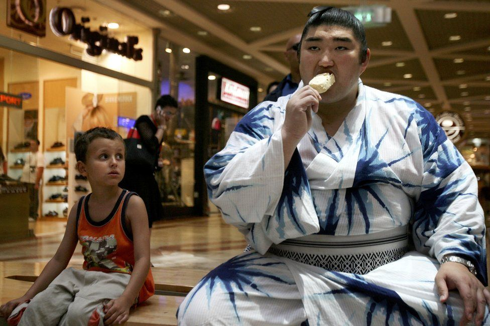 Japanese sumo wrestler Sekiwake Kotomitsuki eats ice cream while a little boy watches him during a visit to a Tel Aviv shopping centre