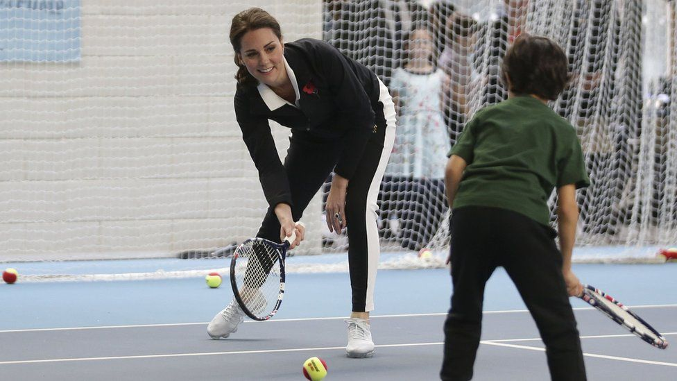 The Duchess of Cambridge playing tennis with a boy