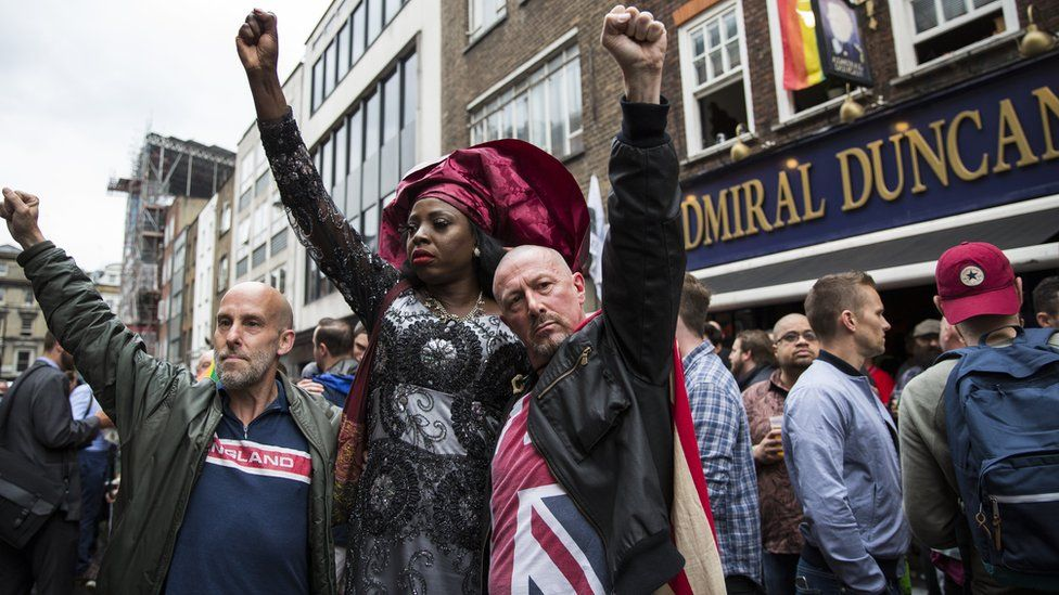 People in London hold their fist in the air during a vigil for hate crime victims