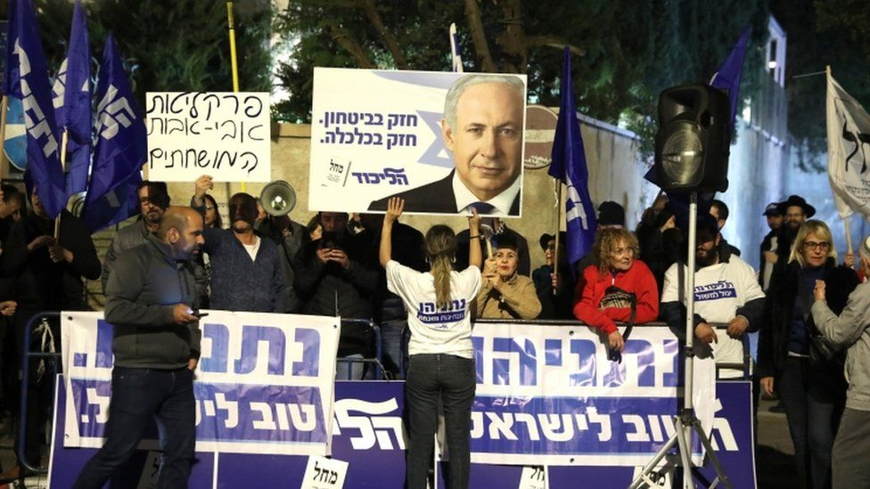 Supporters of Mr Netanyahu stand outside the prime minister's residence with signs