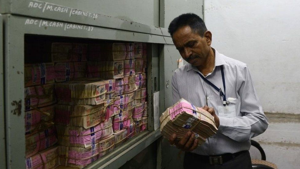 An Indian bank employee looks at deposited old denomination 1000 rupee currency notes in a bank vault in Ahmedabad on November 11, 2016.