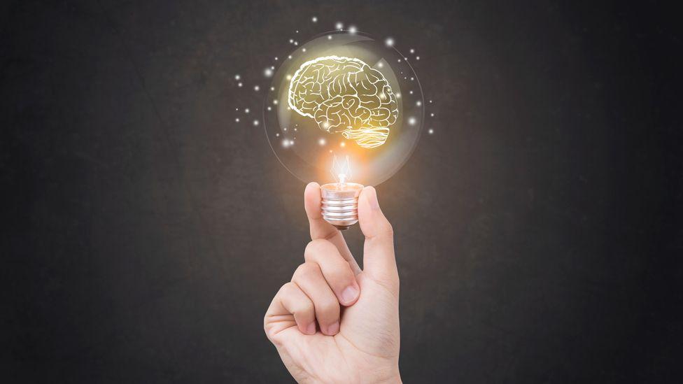 A hand holding a light bulb containing a brain