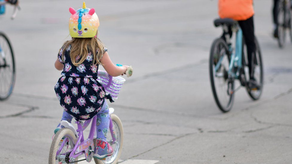 Child cycling behind an adult