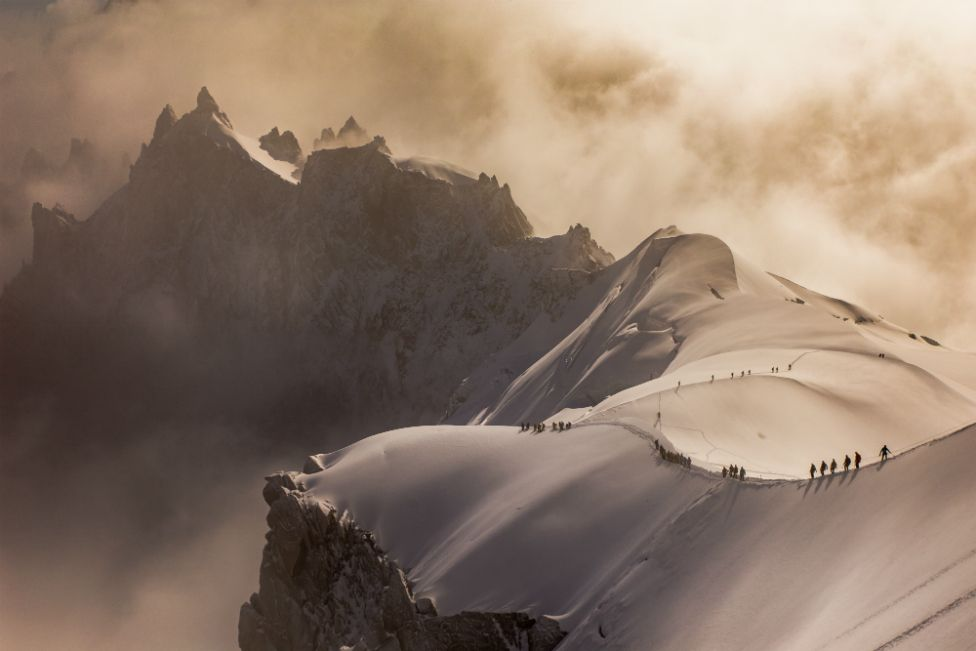 Climbers descend a snow ridge on the French Alps