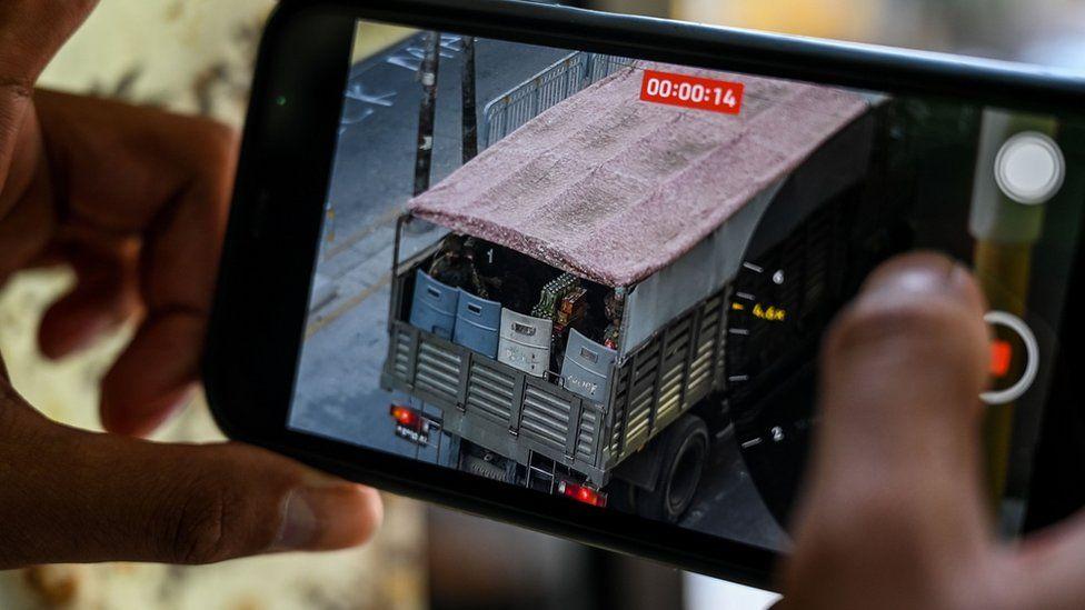 Seseorang memegang ponsel yang menunjukkan video tentara sedang melihat keluar dari truk di Yangon pada 28 Februari 2021