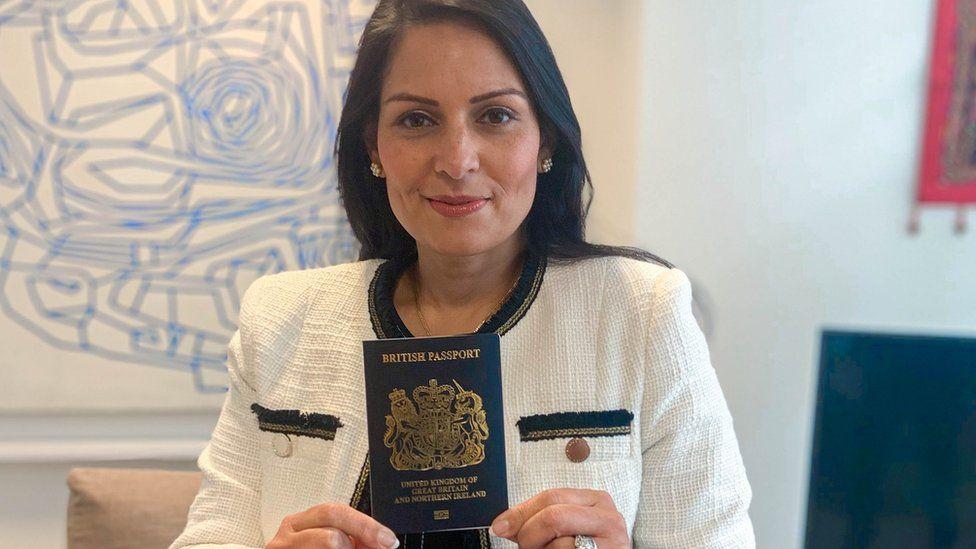 Home Secretary Priti Patel holding a blue passport