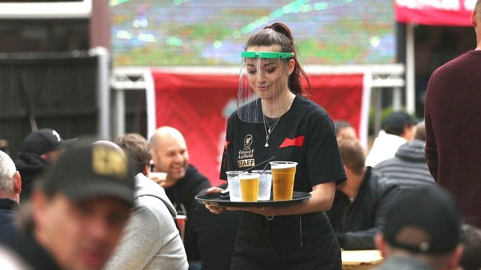 Waitress carrying drinks through a pub garden with football on
