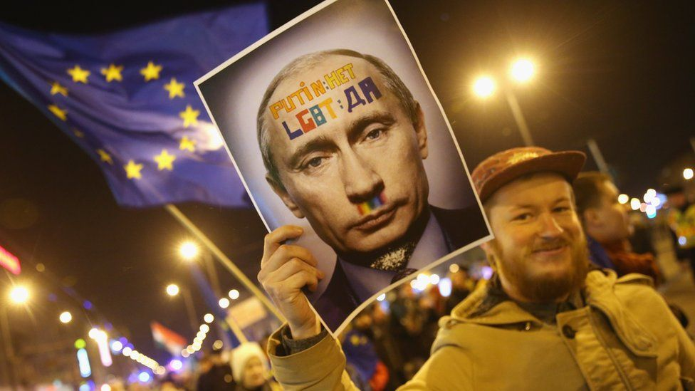 Demonstrators, including one bearing a portrait of Russian President Vladimir Putin and another waving a flag of the European Union, march to protest against a visit to Budapest by Putin as well as against the government of Hungarian Prime Minister Viktor Orban in February 2015 in Budapest, Hungary
