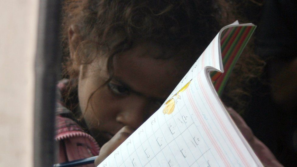 A Yemeni young girl writes in an exercise book inside a minibus turned into a mobile classroom in Sanaa