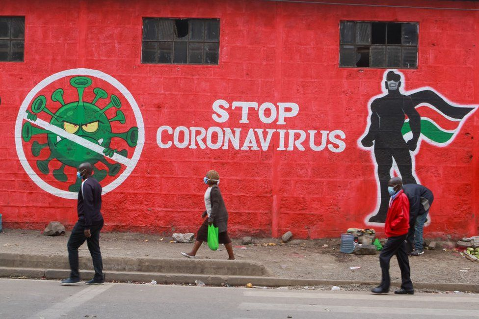 Kenyans walk past an informative mural about the Coronavirus along Haile Selassie avenue in Nairobi.
