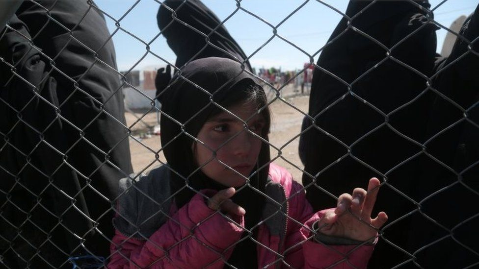 A girl looks through a chain linked fence at al-Hol displacement camp in Hasaka governorate, Syria on 8 March 2019