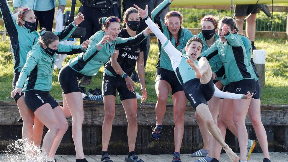 The Cambridge crew celebrates by throwing their cox Dylan Whittaker into the water after winning the 75th Women's Boat Race
