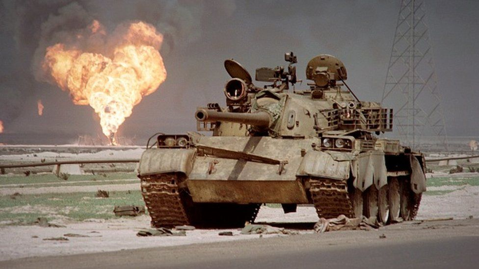 An abandoned Iraqi Soviet-made tank sits in the Kuwaiti desert in 1991 as an oil well at the Al-Ahmadi oil field is burning.