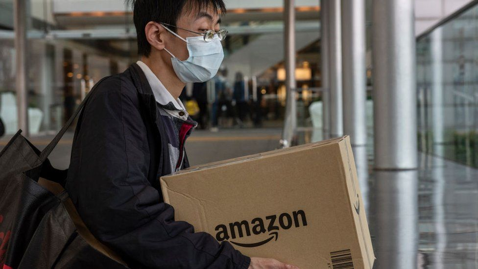 A man wearing a surgical mask carries an Amazon delivery box in Hong Kong