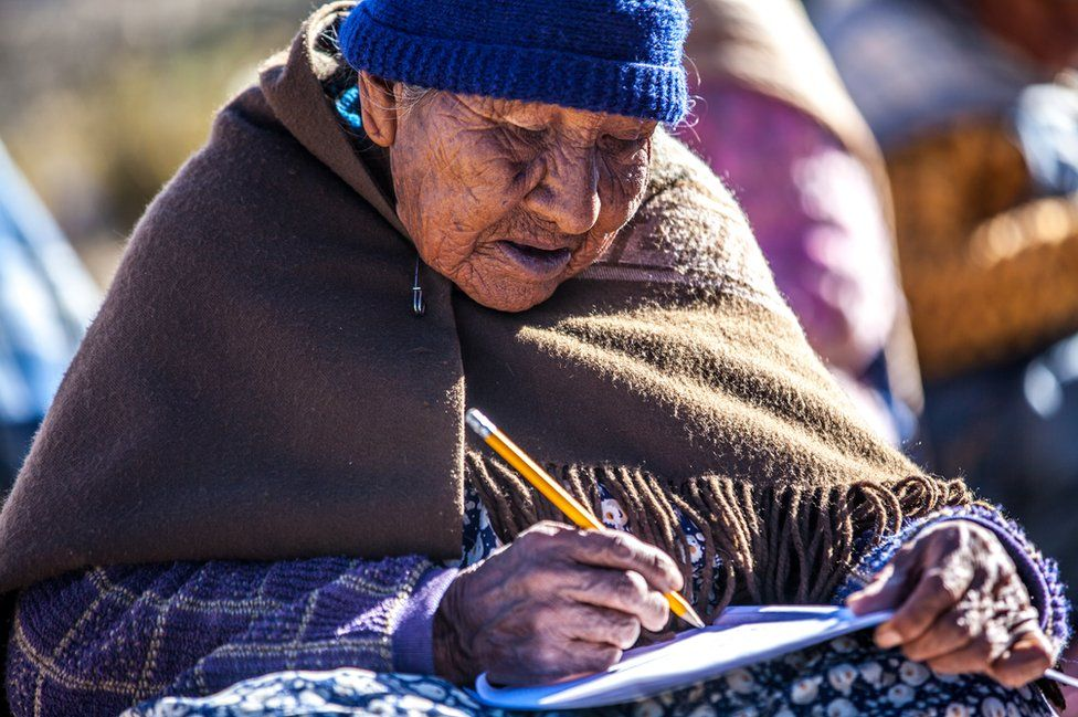 An elderly student practices writing in a notebook