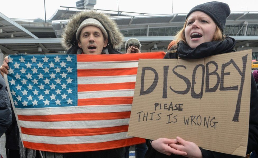 Demonstrators with a US flag and a sign urging protest stand at JFK airport