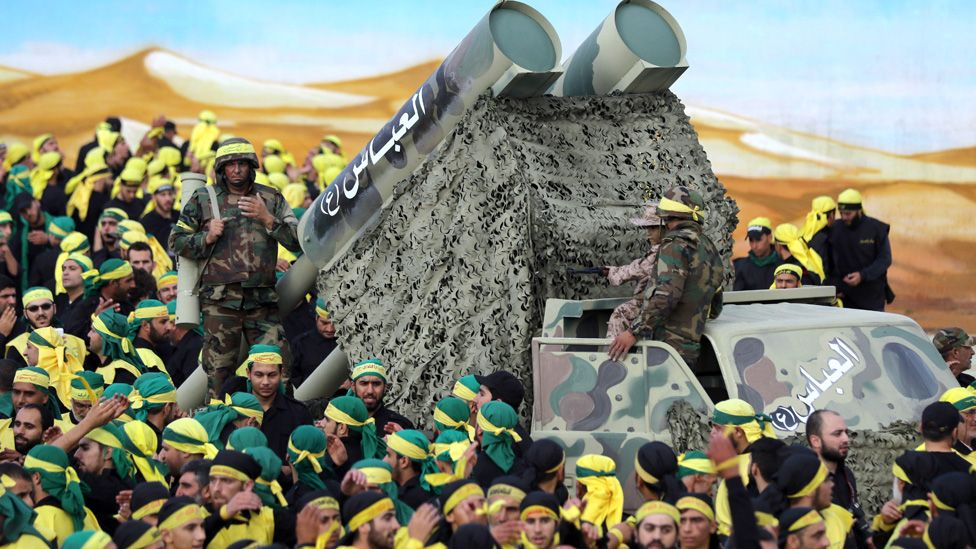Members of Lebanon's powerful Shiite movement Hezbollah parade with a mock missile launcher during a rally on the thirteenth day of the mourning period of Muharram, which follows the tenth day of Ashura, in the southern Lebanese city of Nabatiyeh, on October 27, 2015.