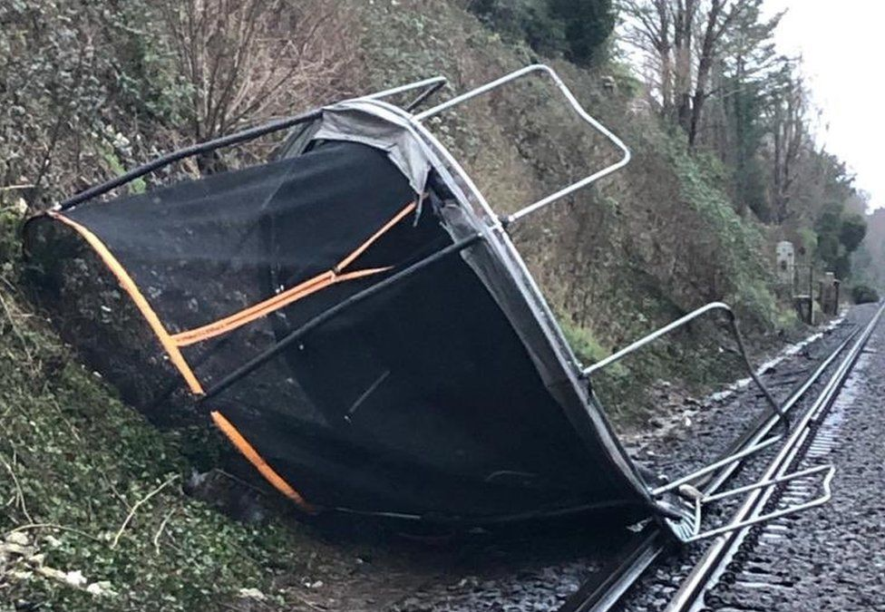 A trampoline blown onto the train line