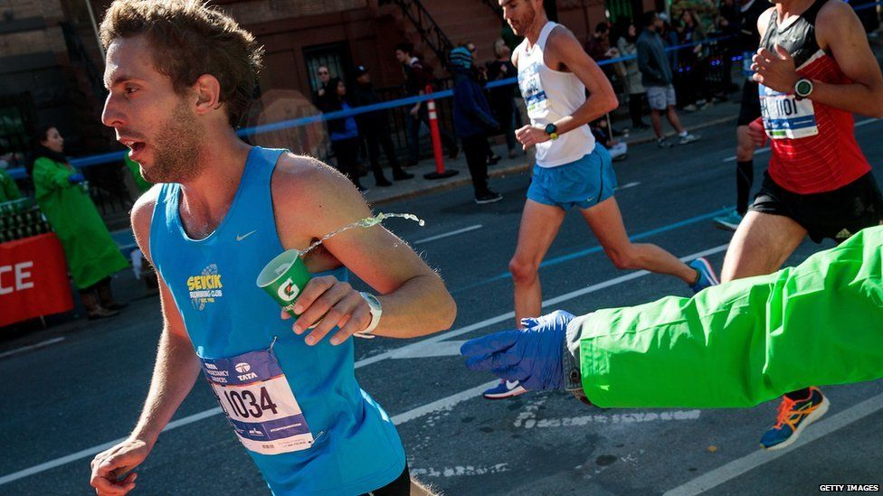 A runner grabs a cup of Gatorade as he runs on Lafayette Avenue during the 2016 TCS New York City Marathon,