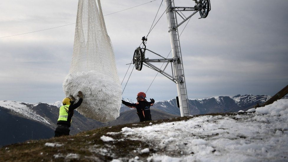 Two men help a helicopter carrying snow near Luchon in French Pyrenees