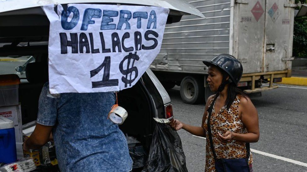 "A woman buys a ""hallaca"" -typical venezuelan Christmas dish- with US dollars in a street of Caracas on November 19, 2019."