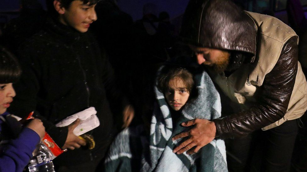 A girl is wrapped in a blanket after being evacuated from rebel-held Aleppo on 21 December 2016