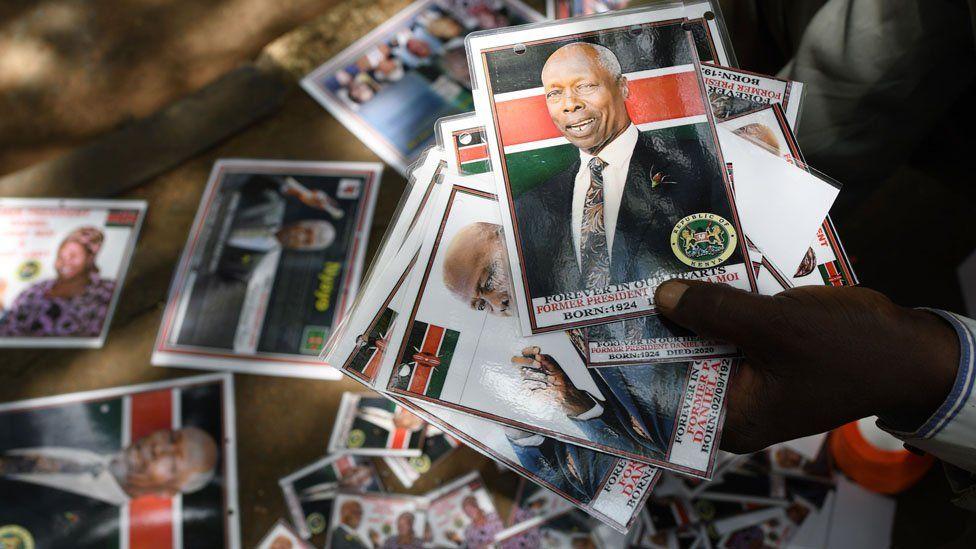 "A man sells badges bearing the photo of late former Kenya""s President Daniel Arap Moi, outside Parliament Buildings"