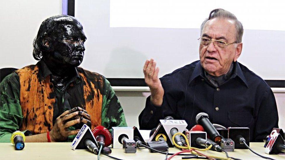 Indian activist Sudheendra Kulkarni (L), whose face was blackened by ink in an alleged attack, looks on as former Pakistani foreign minister Khurshid Mahmud Kasuri speaks to media in Mumbai on 12 October 2015.
