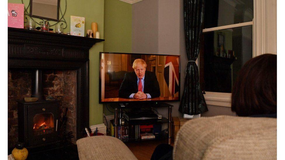 Woman watching Boris Johnson on television