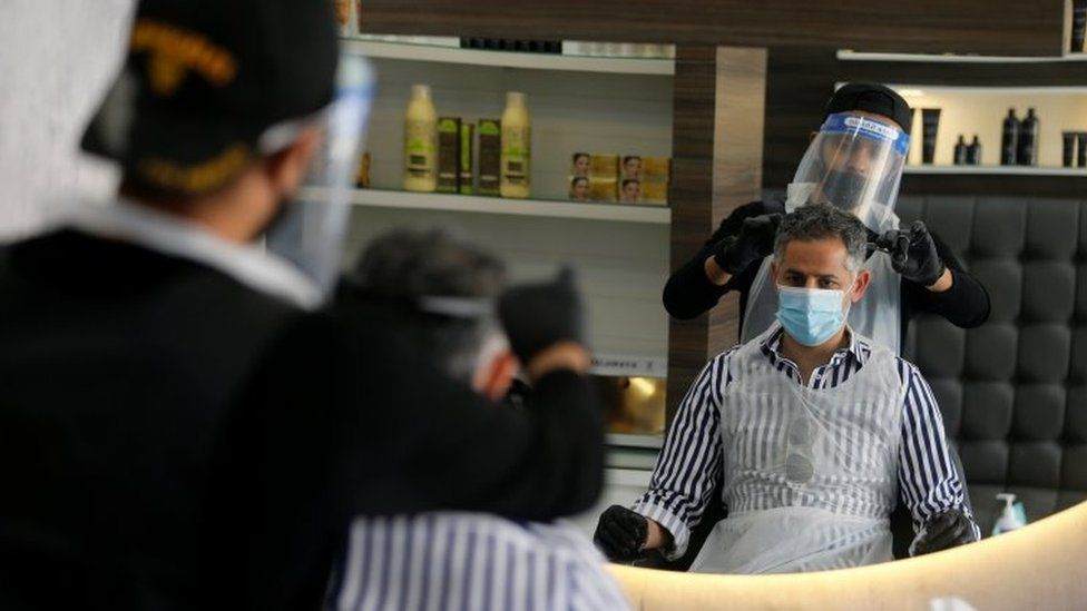 A man has his hair cut by a barber wearing protective equipment in Isa Town, Bahrain (27 May 2020)