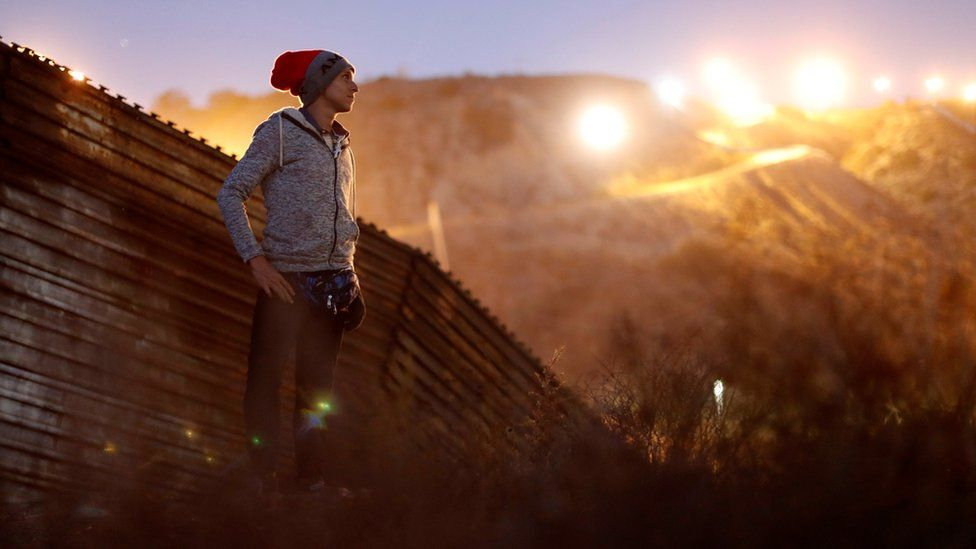 Kevin Jorge Gallardo Antunez, a migrant from Honduras, poses in front of the border wall
