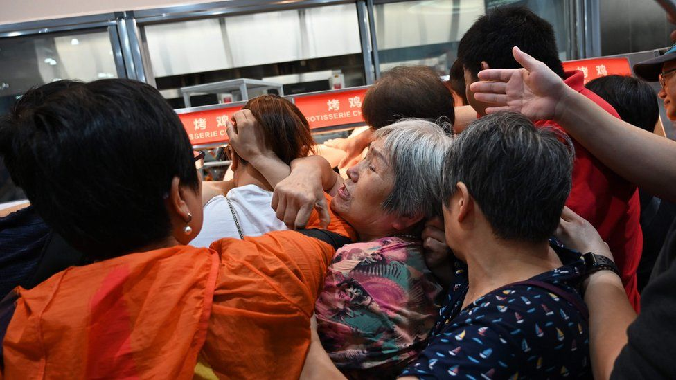 People jostle for cooked chickens